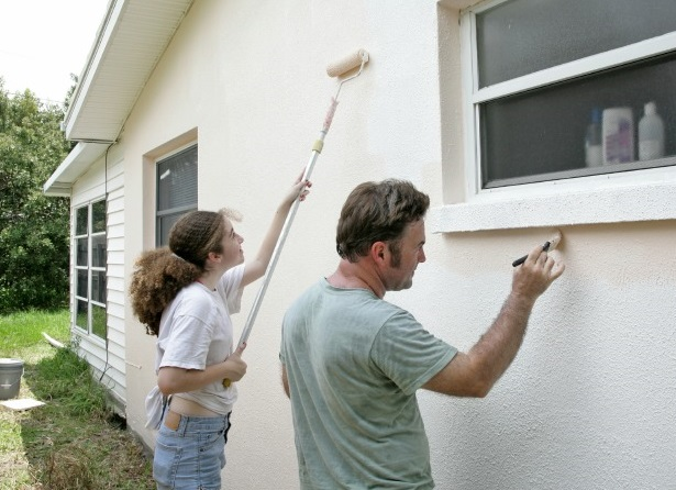 A father and daughter painting their house together.
